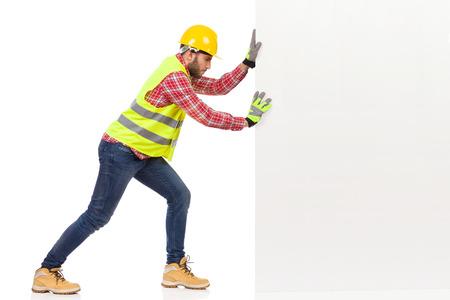 Mann in der reflektierenden Weste und im gelben Helm drückt eine weiße Wand. Seitenansicht. Studioaufnahme in voller Länge isoliert auf Weiß.