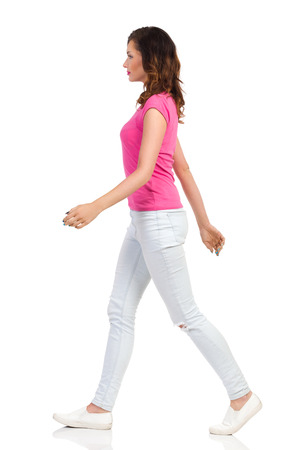 Young woman in pink t-shirt, light jeans and white sneakers is walking and looking away. Side view. Full length studio shot isolated on white.