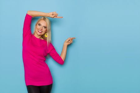 Beautiful blond woman in pink sweater is standing, looking at camera, and pointing. Three quarter length studio shot on blue background. Stock Photo