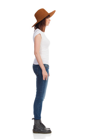Serious young woman in white t-shirt, jeans, suede hat and black boots is standing and looking away. Side view. Full length studio shot isolated on white.
