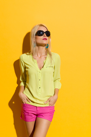 Serious beautiful blond woman in yellow shirt, pink shorts and sunglasses is looking away. Three quarter length studio shot on yellow background. Stock Photo