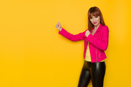 Smiling young woman in pink jacket and black leather trousers is clenching fist and looking at camera. Three quarter length studio shot on yellow background.