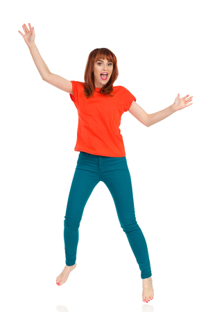 Barefoot young woman in orange t-shirt and teal pants is jumping with arms outstretched and shouting. Front view. Full length studio shot isolated on white.