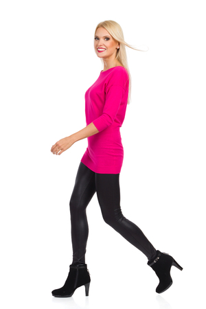 Blond woman in black leggings, high heels and pink sweater is walking, smiling and looking at camera. Side view. Full length studio shot isolated on white. Stock Photo