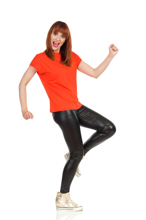 Young woman in orange t-shirt, black leather pants and gold sneakers is walking funny, looking at camera and talking. Side view. Full length studio shot isolated on white.
