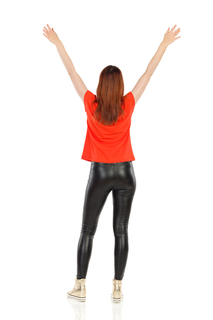 Woman in black leather pants, gold sneakers and orange shirt is standing with arm raised. Rear view. Full length studio shot isolated on white.