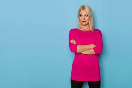 Beautiful blond woman in pink sweater is standing with arms crossed and looking away. Three quarter length studio shot on turquoise background.