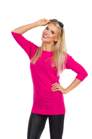 Beautiful blond woman in black leggings and pink sweater is holding sunglasses on head, looking at camera and smiling. Three quarter length studio shot isolated on white.