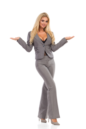 Beautiful blond woman in gray suit and high heels is standing with hands raised, presenting and looking at camera. Front view. Full length studio shot isolated on white.