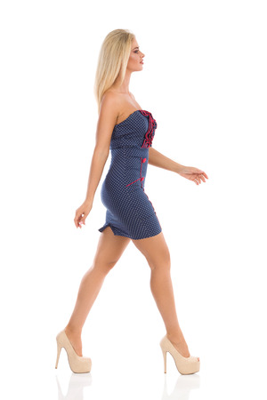 Beautiful blond woman in blue dotted mini dress and high heels is walking and looking away. Full length studio shot isolated on white.