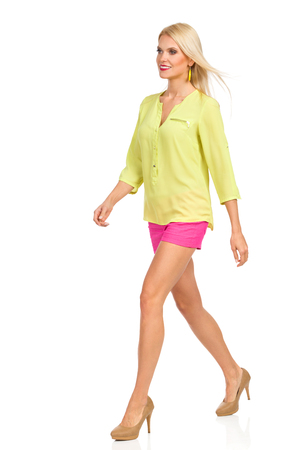 Beautiful blond woman in pink shorts, green shirt and high heels is walking and looking away. Front side view. Full length studio shot isolated on white.