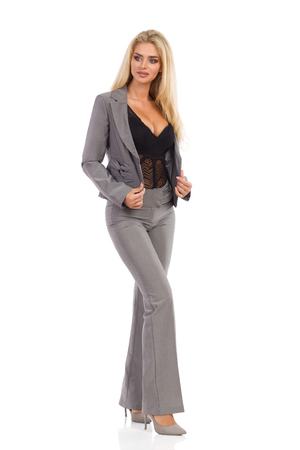 Beautiful blond woman in gray suit and high heels is standing and looking away. Front view. Full length studio shot isolated on white. Stockfoto