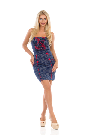 Beautiful blond woman in blue dotted mini dress and high heels is standing and looking at camera. Full length studio shot isolated on white.