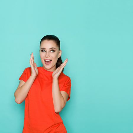 Excited beautiful young woman in orange shirt is holding hands raised, looking away and shouting. Waist up studio shot on turquoise background.