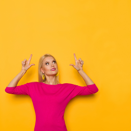 Beautiful blond woman in pink sweater is standing, looking away and pointing up. Waist up studio shot on yellow background.
