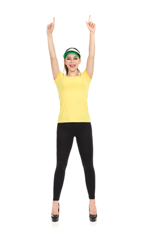 Young woman in yellow shirt, black leggings and high heels is holding arms raised, pointing up and talking. Full length studio shot isolated on white.