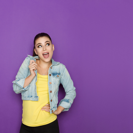 Excited beautiful young woman in jeans jacket is looking away and talking. Waist up studio shot on purple background.