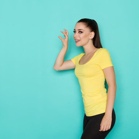 Beautiful young woman in yellow shirt is standing with hand raised, looking at camera and trying to hold something. Three quarter length studio shot on turquoise background.