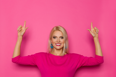 Beautiful blond woman in pink sweater is looking at camera and pointing up. Waist up studio shot on pink background.