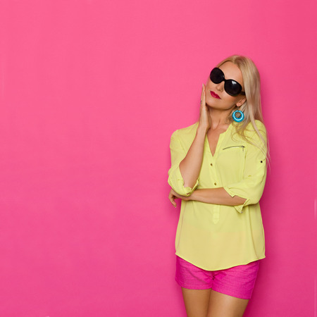 Pensive beautiful blond woman in yellow shirt and pink shorts is looking away and dreaming. Three quarter length studio shot on pink background.