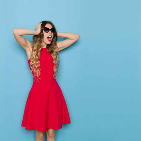 Beautiful young woman in red mini dress and sunglasses is holding head in hands, looking at camera and shouting. Three quarter length studio shot on blue background. Stock Photo