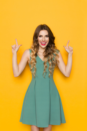 Happy beautiful young woman in green dress is looking at camera, pointing up and talking. Front view. Three quarter length studio shot on yellow background.