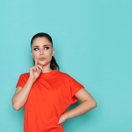 Beautiful young woman is holding finger on chin, looking away and thinking. Waist up studio shot on turquoise background.