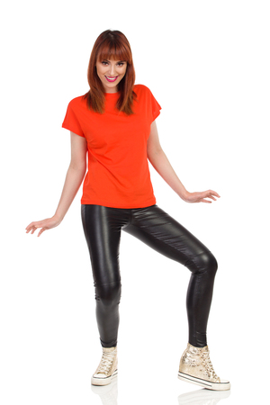 Young woman in orange t-shirt, black leather pants and gold sneakers is standing legs apart, looking at camera and smiling. Front view. Full length studio shot isolated on white.