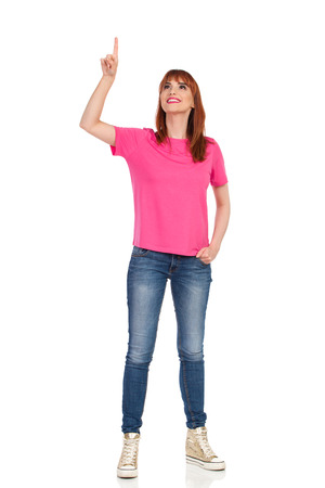 Young woman in pink t-shirt, jeans and gold sneakers is standing with arm raised, touching something and looking up. Front view. Full length studio shot isolated on white. Foto de archivo