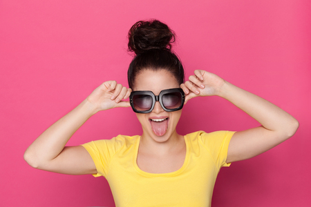 Beautiful young woman in yellow top and big sunglasses is sticking out tongue. Studio portrait on pink background.