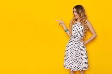 Beautiful young woman in white dotted summer dress is  pointing at copy space, looking away and talking. Three quarter length studio shot on yellow background.