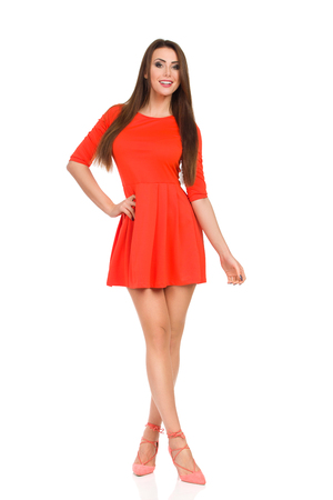Smiling fashion model in red mini dress and high heels is standing with legs crossed and looking at camera. Full length studio shot Isolated on white.