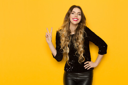Beautiful young woman in black sequin top and leather trousers is showing peace hand sign and smiling. Three quarter length studio shot on yellow background. 版權商用圖片