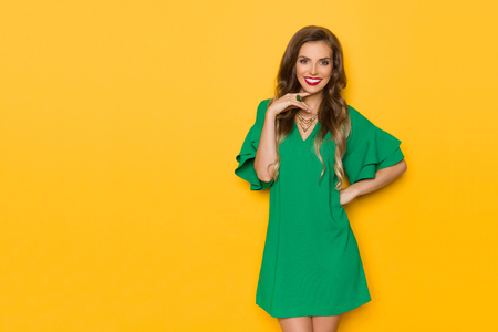 Beautiful young woman in green mini dress is posing with hand on chin, looking at camera and smiling. Three quarter length studio shot on yellow background. 写真素材