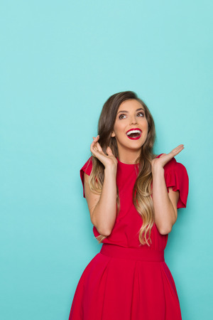 Beautiful young woman in red dress is looking up, laughing and gesturing Three quarter length studio shot on turquoise background.