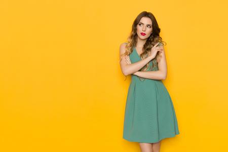 Portrait of pensive beautiful young woman in green mini dress. Three quarter length studio shot on yellow background.
