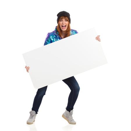 Young woman in vibrant and shiny down jacket, winter cap, jeans and sneakers is standing, holding white placard and shouting. Full length studio shot isolated on white. 版權商用圖片