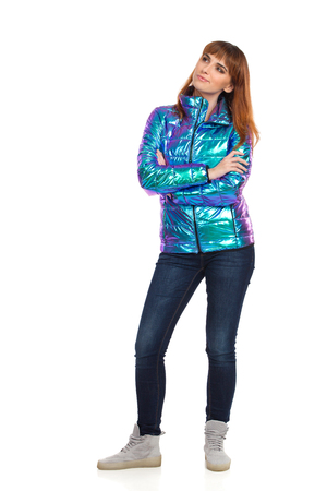 Skeptic young woman in vibrant and shiny down jacket, jeans and sneakers is standing with arms crossed and looking away. Front view. Full length studio shot isolated on white. Фото со стока