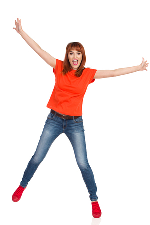 Happy young woman in orange shirt, jeans and red sneakers is standing on one leg, holding arms outstretched and shouting. Full length studio shot isolated on white. Foto de archivo
