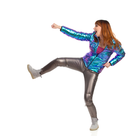 Young woman in shiny pants, vibrant down jacket and sneakers is kicking and shouting. Side view. Full length studio shot isolated on white. 免版税图像