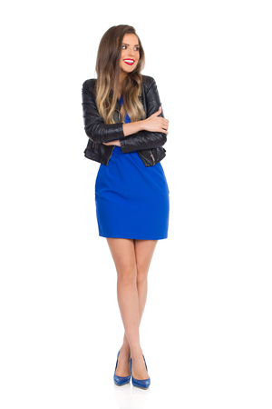 Beautiful young woman in blue mini dress, leather jacket and high heels is standing, with arms and legs crossed, looking away and smiling. Full length studio shot isolated on white.