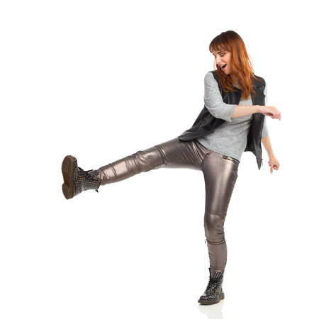 Young woman in gray blouse, shiny pants and black boots is kicking something. Side view. Full length studio shot isolated on white. Stock Photo