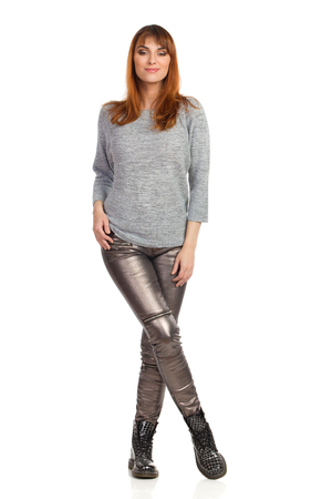 Young woman in gray blouse, shiny pants and black boots is standing with legs crossed and looking at camera. Front view. Full length studio shot isolated on white.