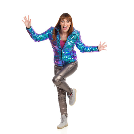 Young woman in vibrant down jacket, shiny pants and sneakers is standing on one leg with arms outstretched and shouting. Front view. Full length studio shot isolated on white.