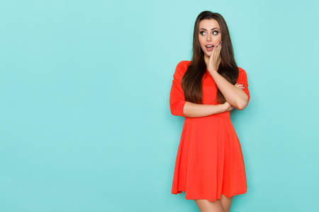 Surprised beautiful young woman in red mini dress is holding hand on chin and looking away. Three quarter length studio shot on blue background. Stock Photo