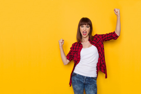 Young woman in red lumberjack shirt and jeans is holding arms raised, clenching fists and shouting. Three quarter length studio shot on yellow background. Stock Photo