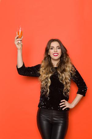 Schöne junge Frau in schwarzem Paillettenoberteil und Lederhose hält ein Glas Wein, röstet und lächelt. Dreiviertellange Studioaufnahme auf orangem Hintergrund.