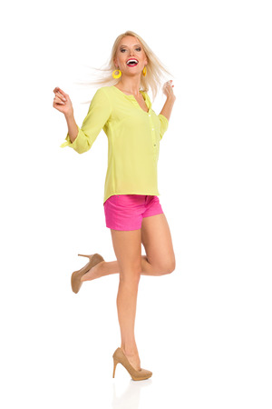 Beautiful blond woman in pink shorts, yellow shirt and high heels is standing on one leg, dancing and laughing. Full length studio shot isolated on white.