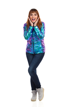 Young woman in vibrant and shiny down jacket, jeans and sneakers is standing, looking at camera, holding head in hands and laughing. Front view. Full length studio shot isolated on white.