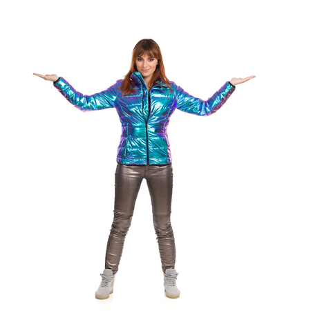 Young woman in vibrant and shiny down jacket, jeans and sneakers is standing, holding hands raised, showing something and looking at camera. Front view. Full length studio shot isolated on white.